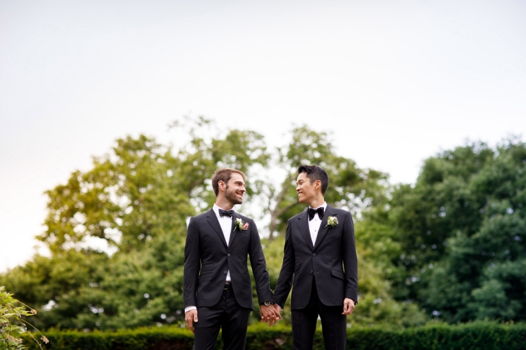 Two grooms look at each other on their wedding day, dressed in black suits.