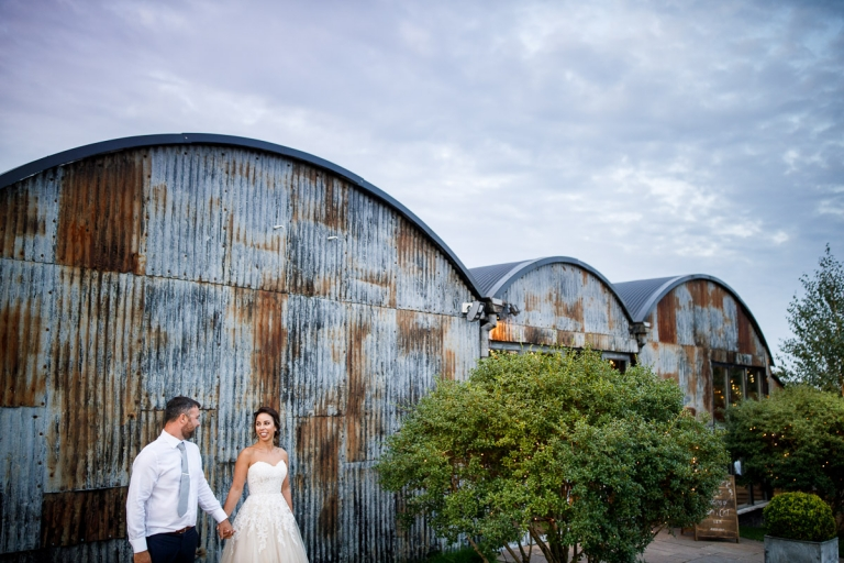Stone Barn - Couple stood outside the corrugated iron front of the barn. Blog featuring their wedding in an English Barn in the Cotswolds.