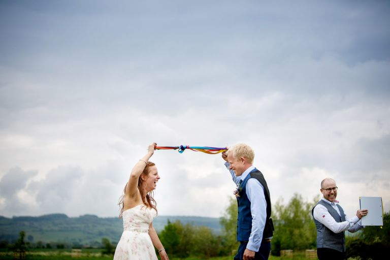 Couple do a handfasting at their humanist outside wedding - they use very colourful personalised ribbons.