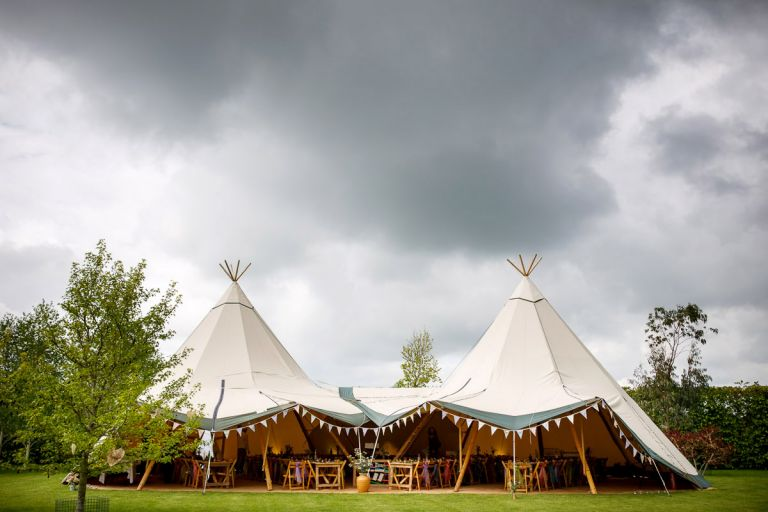 Tipi decorated for a wedding reception with lots of bunting and colourful scarfs.